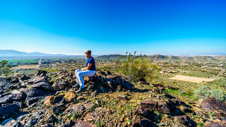 sates: Senior woman enjoying the view from the top of the National Trail near the San Juan Trail Head in the mountains of South Mountain Park in Maricopa County near the city of Phoenix, Arizona, USA Stock Photo