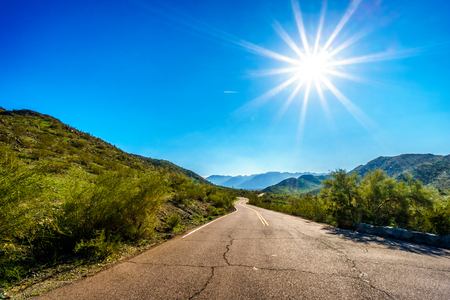 sates: Sun casting its sun rays on the East San Juan Road near the San Juan Trail Head in the mountains of South Mountain Park in Maricopa County near the city of Phoenix, Arizona, USA Stock Photo