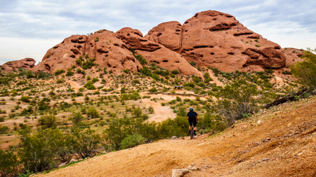 sates: Biking down the red sandstone buttes of Papago Park, with its many caves and crevasses caused by erosion under cloudy sky, in the city of Tempe, Arizona in the United States of America