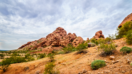 The red sandstone buttes of Papago Park, with its many caves and crevasses caused by erosion under cloudy sky, in the city of Tempe, Arizona in the United States of America
