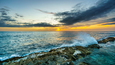 oahu: Sunset over the horizon with a few clouds and waves crashing on the rocky shores of the west coast of the tropical Hawaiian island of Oahu Stock Photo