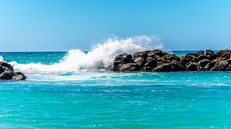 Waves crashing on the barriers made of large rocks at the resort community of Ko Olina on the West Coast of the Hawaiian island of Oahu. The barriers make the lagoons safe for swimming Stock Photo