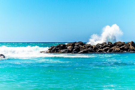 oahu: Waves crashing on the barriers made of large rocks at the resort community of Ko Olina on the West Coast of the Hawaiian island of Oahu. The barriers make the lagoons safe for swimming Stock Photo