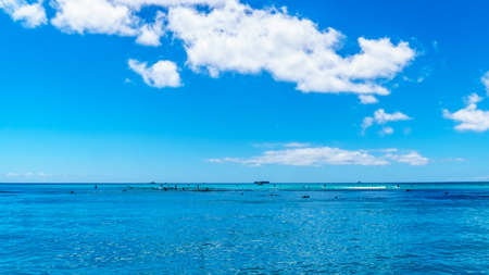 The beautiful waters of Waikiki beach under blue and partly cloudy sky makes it one of the worlds most famous beaches. Located in Honolulu on the Hawaiian island of Oahu Stock Photo