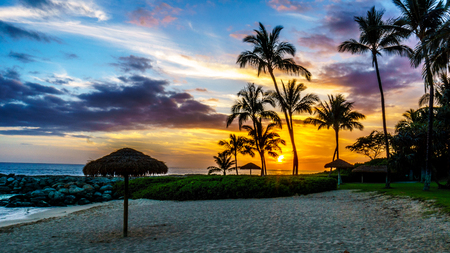 Sunset over the Lagoon and beach with Palm trees and colorful sky at the resort community of Ko Olina on the West Coast of the Hawaiian island of Oahu Stock Photo
