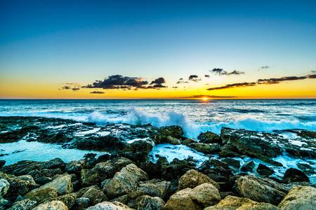 いくつかの雲と熱帯ハワイ オアフ島の西海岸の岩の海岸にクラッシュ波と水平線に沈む夕日