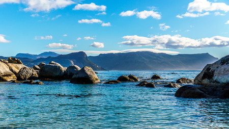penguins on beach: Large granite boulders at Boulders Beach, a popular nature reserve and home to a colony of African Penguins, in the village of Simons Town in the Cape Peninsula of South Africa Stock Photo