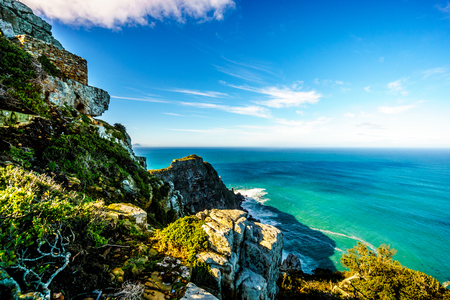 Rugged and steep cliffs of Cape Point in the Cape of Good Hope Nature Reserve on the southern tip of the Cape Peninsula in South Africa surrounded by the turquoise waters of the Atlantic Ocean