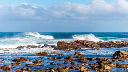 Waves of the Atlantic Ocean breaking on the rocky shores of Cape of Good Hope in Cape Point Nature Reserve on the Cape Peninsula in South Africa Stock Photo
