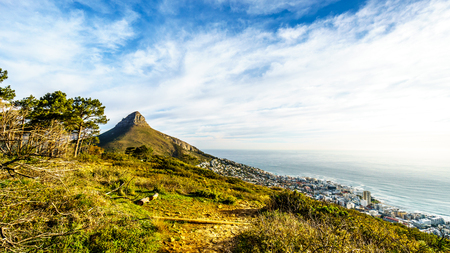 un setting over Lions Head and Camps Bay. Viewed from the top of Signal Hill at Cape Town, South Africa Stock Photo
