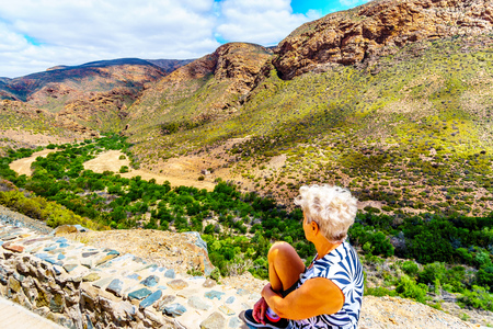 Senior woman looking at the completely dry Huisrivier along the Huis River Pass on highway 62 between Ladismith and Calitzdorp in the Little Karoo of the Western Cape Province of South Africa