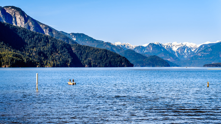 Fishing on Pitt Lake with the Snow Capped Peaks of the Golden Ears, Tingle Peak and other Mountain Peaks of the Coast Mountain Range in the Fraser Valley of British Columbia, Canada