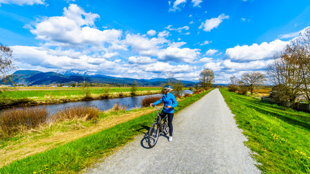 Senior woman biking along the Alouette River on the dyke surrounding Pitt Polder at the town of Maple Ridge in British Columbia, Canada