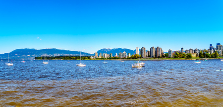 Panorama View of the Skyline of the West End of the city of Vancouver British Columbia with the busy False Creek inlet popular with boaters in the foreground Stock Photo
