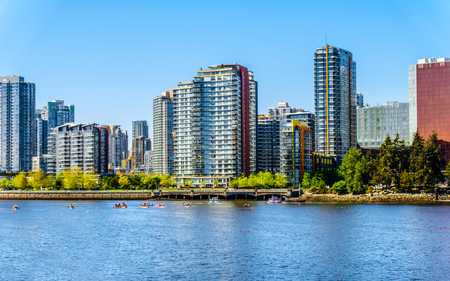 Skyline of Vancouver, British Columbia from False Creek Inlet under clear blue sky