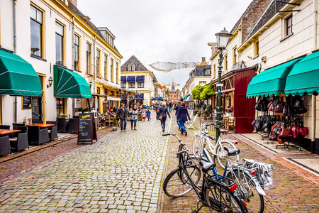 Elburg, the Netherlands - Oct. 25, 2014: The cobblestone main street and popular shopping street in the center of the historic Dutch fishing village of Elburg in the heart of Holland Editorial