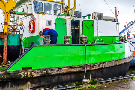 Urk, The Netherlands - Oct. 17, 2014: Welder repairing Bollards on a Large Cutter Suction Dredger vessel anchored for repairs in the historic fishing village of Urk in the Netherlands Editorial