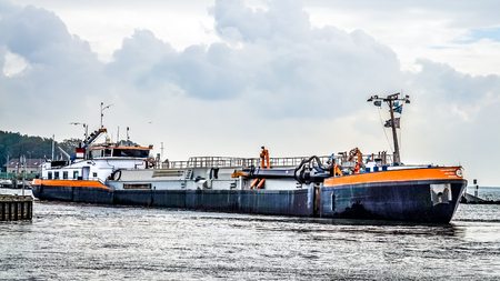 Urk, The Netherlands - Oct. 17, 2014: Large Cutter Suction Dredger vessel entering the harbor of the historic fishing village of Urk in the Netherlands Editorial