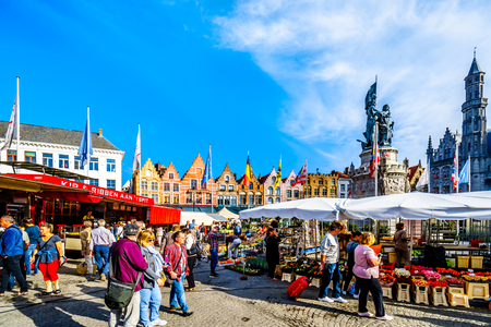 Open air market at the central Markt (Market Square) in the heart of Bruges, Belgium surrounded by the colorful medieval houses with Step Gables lining the market