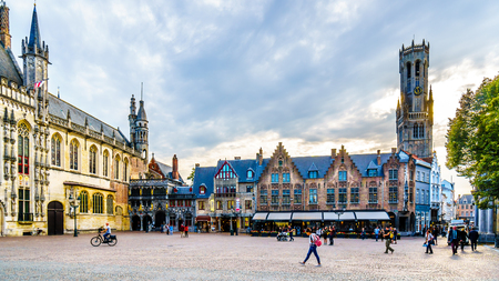 Historic buildings of the Town Hall and Basilica of the Holy Blood on Burg Square with the Belfry Tower in the background in the medieval city of Bruges, Belgium