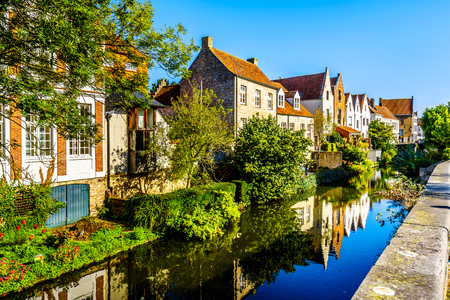 Reflections of medieval houses houses in the waters of a canal in Bruges, Belgium