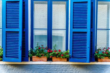 Blue windows with Shutters and red geraniums on the window sill at a house in the historic city of Bruges, Belgium