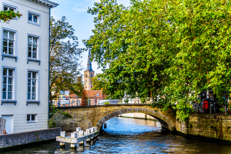 Stone Bridge at the Hoogstraat from the Groenerei and Coupure canals in Bruges, Belgium with the St. Anna Church tower in the background
