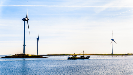 Fishing Boat and Wind Turbines at the Oosterschelde inlet at the Neeltje Jans island at the Delta Works Storm Surge Barrier
