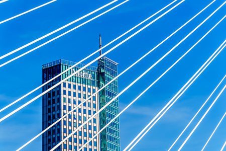 Rotterdamthe Netherlands - Sept. 26, 2018: Modern architectural High Rise buildings viewed through cables of the Cable-Stayed Erasmus Bridge over the Nieuwe Maas River in Rotterdam Redactioneel