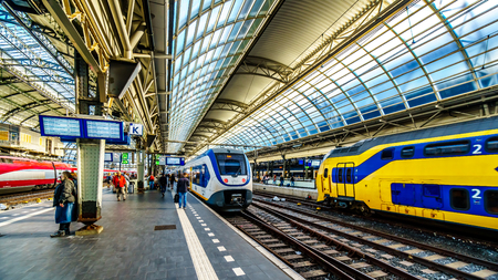 Amsterdam, Noord Holland/the Netherlands - Oct. 3 2018: Passengers waiting for their trains at the busy train station of Amsterdam Centraal Redactioneel