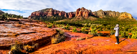 Senior woman taking a photo of the landscape of Cathedral Rock and other red rock mountains surrounding the town of Sedona in northern Arizona in Coconino National Forest, United States of America