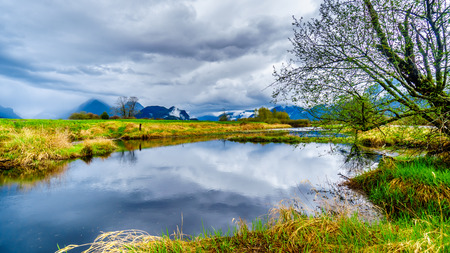 Dark rain clouds on a cold spring day at over the Pitt River and the lagoons of Pitt-Addington Marsh in Pitt Polder near Maple Ridge in British Columbia, Canada