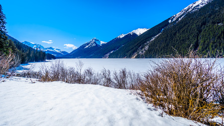 Frozen Duffey Lake and the snow capped peaks around  lake which runs along Highway 99 between Pemberton and Lillooet, British Columbia, Canada Stock fotó