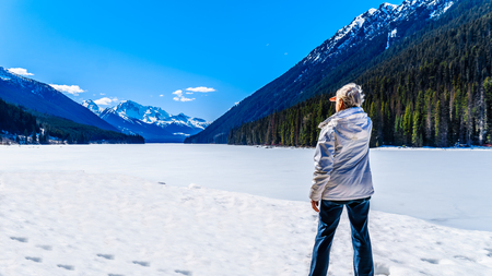 Senior woman enjoying the view of frozen Duffey Lake and the snow capped peaks around  lake. Mount Rohr at the south end of the lake along Highway 99 between Pemberton and Lillooet, British Columbia Stockfoto