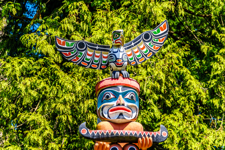 The top of the colorful 'Ga'akstalas Totem Pole' depicting a Quolous, a legendary bird. One of the most colorful and intricately carved totem poles at Stanley Park