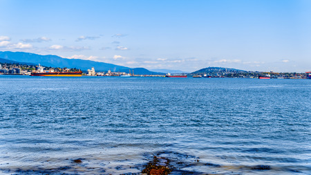View of the Vancouver Harbor with the Second Narrows Bridge in the background. Viewed from the Stanley Park Seawall pathway
