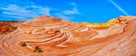 Panorama View of the famous Wave Rock among the colorful red, yellow and white banded rock formations at the end of the Fire Wave Trail in the Valley of Fire State Park in Nevada, USA
