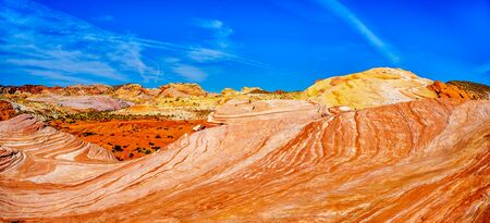 Panorama of the famous Wave Rock among the colorful red, yellow and white banded rock formations at the end of the Fire Wave Trail in the Valley of Fire State Park in Nevada, USA