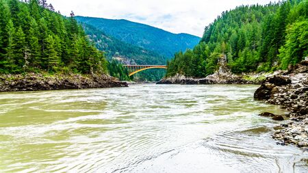 The mighty Fraser River, with the the arch shaped steel structure of the Alexandra Bridge on the Trans Canada Highway in the distance in BC, Canada