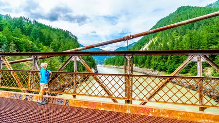 Senior woman on the historic Second Alexandra Bridge between Spuzzum and Hell's Gate along the Trans Canada Highway in British Columbia, Canada