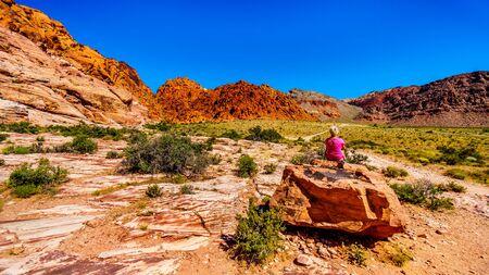 Ältere Frau sitzt auf einem großen roten Felsen beim Wandern auf dem Guardian Angel Trail im Red Rock Canyon National Conservation Area in der Nähe von Las Vegas, Nevada, USA,