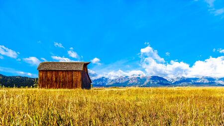 An abandoned Barn at Mormon Row with in the background cloud covered Peaks of the Grand Tetons In Grand Tetons National Park near Jackson Hole, Wyoming, United States