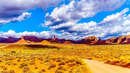 The gravel road that runs past the Red Sandstone Buttes and Pinnacles in the semi desert landscape in the Valley of the Gods State Park near Mexican Hat, Utah, United States