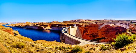 Panorama View of the Glen Canyon Dam with Lake Powell behind the dam, created by the Colorado River. Viewed from the Dam Overlook near Page, Arizona, United States