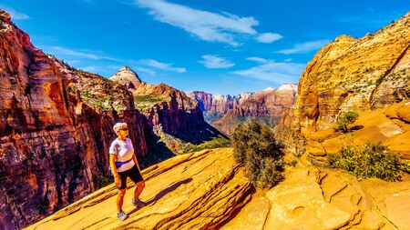 Active Senior Woman enjoying the view of the mountains surrounding Zion Canyon from the top of the Canyon Overlook Trail in Zion National Park, Utah, United States Stock Photo