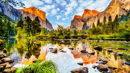 Sunset glow over El Capitan on the left and Cathedral Rocks, Sentinel Rock and Bridalveil Fall on the right and reflecting in the calm water of Merced River in Yosemite National Park, California, USA