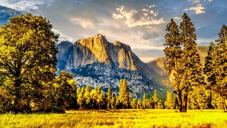 Setting Sun casting glowing sunlight over the almost dry Yosemite Upper Falls at Yosemite Point, the southern shoulder of the Half Dome granite rock in Yosemite National Park, California, USA