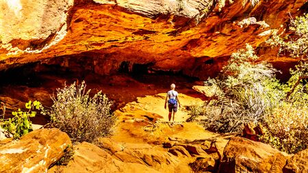 Senior Woman hiking through a Cave on the Canyon Overlook Trail in Zion National Park, Utah, United States