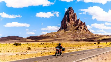Touring Bike Rider passing the rugged peaks of El Capitan and Agathla Peak towering over the desert landscape south of Monument Valley along Highway US Route 163 in northern Arizona, United States