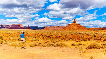 Woman taking a photo of the landscape of Red Sandstone Buttes and Pinnacles in the semi desert landscape in the Valley of the Gods State Park near Mexican Hat, Utah, United States